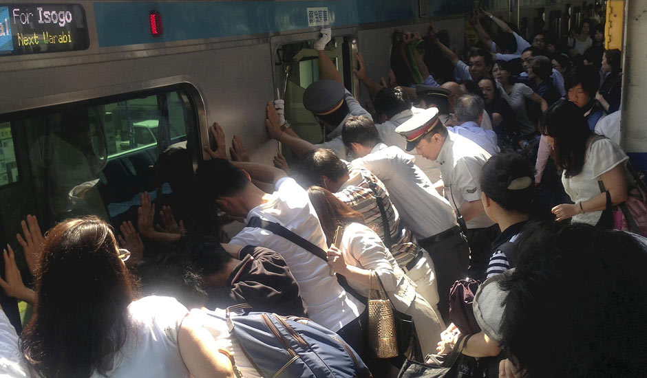 Train passengers and rail staff push a train car to rescue a trapped woman at Minami Urawa station.