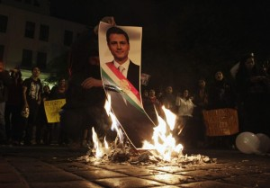 A demonstrator burns a photograph of Mexico's President Enrique Pena Nieto during a protest in support of the 43 missing Ayotzinapa students, in Monterrey